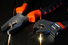 Adjustable wrench and pliers on a black wooden surface with light. Devices for work of the mechanic and the joiner stock image