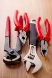 Adjustable wrench, pliers, claw hammer and pliers on the wooden background Stock Photos