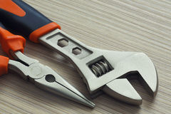 Adjustable wrench and pliers closeup on wooden background. Extreme close up Royalty Free Stock Images
