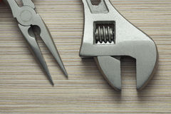 Adjustable wrench and pliers closeup on wooden background. Extreme close up Stock Images