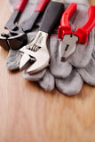 Adjustable wrench, pliers and nail puller on top of the protective gloves Stock Photo