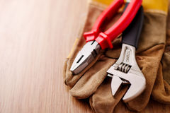 Adjustable wrench and pliers on top of the protective gloves Royalty Free Stock Images