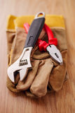 Adjustable wrench and pliers on top of the protective gloves Stock Images
