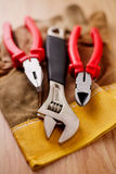 Adjustable wrench, pliers and wire cutters on top of the protective gloves Stock Images