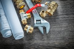 Adjustable wrench plumbing pipe fittings rolled blueprints water. Valve Stock Images