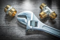 Adjustable wrench threaded pipe fittings on wooden board.  Stock Photography