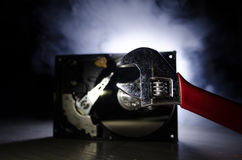 Adjustable wrench turn off a hard disk. On a dark background. Computer repair concept Stock Photo