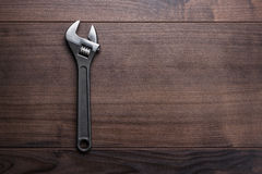Adjustable wrench on the wooden background. Adjustable wrench on the brown wooden background Royalty Free Stock Photo
