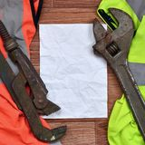 Adjustable wrenches and paper lies of an orange and green signal worker shirts. Still life associated with repair, railway or plu. Mbing works Stock Images