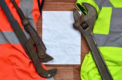 Adjustable wrenches and paper lies of an orange and green signal worker shirts. Still life associated with repair, railway or plu. Mbing works royalty free stock image
