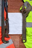Adjustable wrenches and paper lies of an orange and green signal worker shirts. Still life associated with repair, railway or plu. Mbing works royalty free stock photo