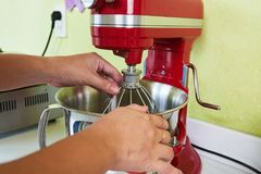 Adjusting beater. Hands of housewife adjusting beater on stand mixer Stock Images