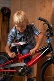 Adjusting bike seat. Boy adjusting seat of his bicycle in garage Stock Image