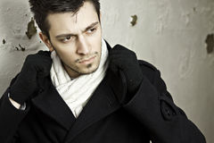 Adjusting collar on black coat. Handsome young man adjusting the collar of his black coloured coat, wearing white scarf and black gloves stock photo