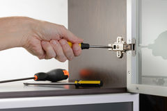Adjusting a Concealed Hinge. A man uses a screwdriver to adjust a concealed hinge fixed on a modern cabinet with a glass door Stock Photo