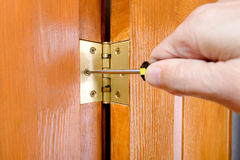 Adjusting a Door Hinge. A man is using a screwdriver to adjust a Door hinge stock image
