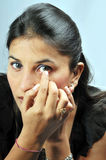 Adjusting eye lens. Indian girl adjusting eye lens Stock Photos