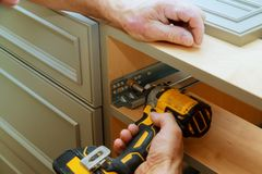 Adjusting fixing cabinet door hinge. Adjustment on kitchen cabinets Stock Photography