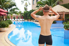 Adjusting goggles. Rear view of sporty man adjusting goggles before swimming Stock Photography