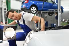 Adjusting the headlights on the car by mechanics in a garage. Smiling car mechanic Royalty Free Stock Photography