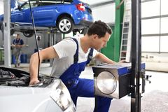 Adjusting the headlights on the car by mechanics in a garage. Backgrounf lift with  car Stock Photo