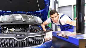 Adjusting the headlights on the car by mechanics in a garage. Closeup Royalty Free Stock Photo