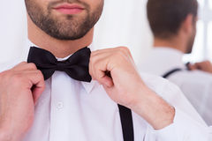 Adjusting his bow tie. Close-up of young man in white shirt adjusting his bow tie while standing against mirror Stock Images
