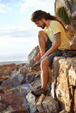Adjusting his laces. Hiker with dreadlocks tying his shoelaces on a mountain Stock Photos