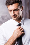 Adjusting his necktie. Royalty Free Stock Photography