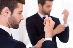 Adjusting his sleeves. Confident young man in formalwear adjusting his sleeves while standing against mirror Royalty Free Stock Photography