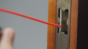 A man greases a lock dog in an interior door, close-up.