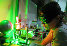 Adjusting laser experiment. Young woman scientist is adjusting laser installation Royalty Free Stock Images