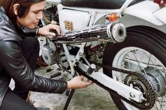 Adjusting Motorcycle Chain. Confident Asian man wearing black leather jacket sitting on haunches while adjusting chain of vintage motorcycle Stock Photo