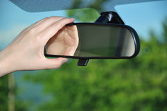 Adjusting rear view mirror. Woman adjusting rear view mirror Royalty Free Stock Images
