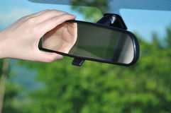 Adjusting rear view mirror. Woman adjusting rear view mirror Stock Photo