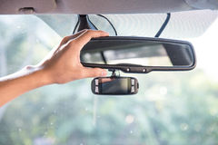 Adjusting The rearview Mirror of a car Royalty Free Stock Image