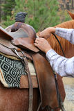Adjusting saddle. Young male cowboy adjusting the saddle on his horse Royalty Free Stock Image