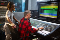 Adjusting sound level. Sound operator and his assistant working in audio studio Royalty Free Stock Images