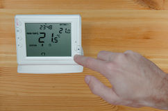 Adjusting the temperature with hand to a wireless thermostat stock photos