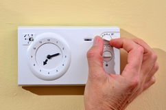Adjusting thermostat to save on heating. Seniors adjusting thermostat to save on heating costs Stock Images