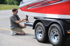 Adjusting Tie Down Straps On Boat Trailer. A Man Adjusting Tie Down Straps On Boat Trailer Royalty Free Stock Photos