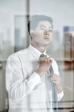 Adjusting tie. Young Asian businessman adjusting tie before work Stock Images