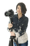 Adjusting to Shoot. An attractive young teen photographer adjusting camera and tripod. On a white background royalty free stock photo