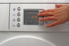 Adjusting a washing machine Stock Photo