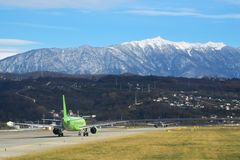 ADLER, RUSLAND Reis Vliegveldmening De Internationale Luchthaven van Sotchi Groen gras tussen banen en mooie bergen  royalty-vrije stock foto