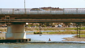 ADLER. RUSSIA - CIRCA AUG 2016: Little boy is swimming in the mountain river under the bridge. With moderate car traffic stock video