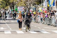Adloyada每年狂欢节的参加者在童话服装乘驾穿戴了一辆自行车在纳哈里亚,以色列 免版税图库摄影