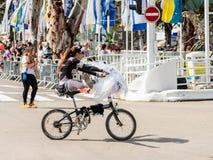 Adloyada每年狂欢节的参加者在童话服装乘驾穿戴了一辆自行车在纳哈里亚,以色列 免版税库存图片