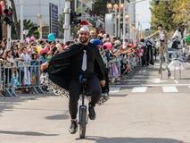 Adloyada每年狂欢节的参加者在童话服装乘驾穿戴了一monocycle在纳哈里亚,以色列 图库摄影