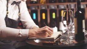 Administrador de vino que mira las botellas de vino y que escribe en cuaderno en la bodega almacen de metraje de vídeo